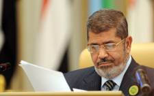 Egypt's President Mohamed Morsi looks at documents at the start of the third Arab Economic, Social and Development Summit, on January 21, 2013, in Riyadh. Picture: AFP