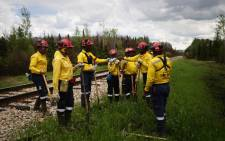 FILE: A group of South African firefighters take a water break as they work to mop-up hot spots in an area close to Anzac, just outside of Fort McMurray, Alberta on 2 June, 2016. Picture: AFP.