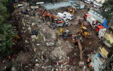 Indian firefighters and rescue workers are seen working at the site of the building collapse in Mumbai on 28 September 2013. Picture: AFP/PUNIT PARANJPE
