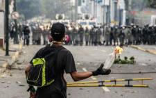 A Venezuelan opposition activist holds a lit Molotov cocktail during clashes with riot police in Caracas on April 10, 2017. Venezuela's political crisis intensified last week when the Supreme Court issued rulings curbing the powers of the opposition-controlled legislature. The court reversed the rulings days later, but the opposition intensified its protests from that moment. FEDERICO PARRA / AFP