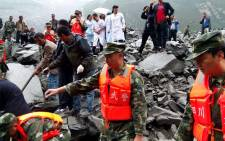 Chinese military police and rescue workers are seen at the site of a landslide in in Xinmo village, Diexi town of Maoxian county, Sichuan province on 24 June, 2017. Picture: AFP.