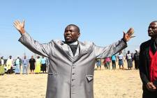 Pastor Sakhumuzi Qiqimana leads a prayer session at the scene of police shootings at Lonmin's Marikana mine on 19 August 2012. Picture: Taurai Maduna/EWN
