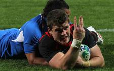 Scott Williams of Wales signals three tries as he is tackled by Ryan De La Harpe of Namibia during the 2011 Rugby World Cup pool D match against Namibia on 26 September 2011. AFP