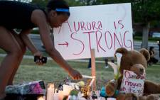 Mourners at a vigil light candles and lay flowers in memory of the 12 victims that were killed at a Batman premier on July 20, 2012 in Aurora, Colorado. Picture AFP