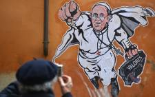 A man takes a picture of a street art mural in Rome showing Pope Francis as a superman.  Picture: AFP