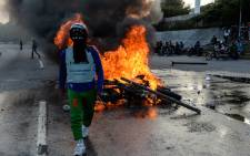 A masked demonstrator stands near a burning motorbike in clashes with the riot police during an anti-government protest in Caracas, on 22 June 2017. Picture AFP.