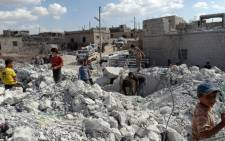 FILE: Syrians check a damaged house following air strikes in the western Aleppo province. Picture: AFP.