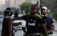 Rebel fighters celebrate on August 25, 2011 after taking control of the southern Tripoli district of Abu Salim. Picture: AFP