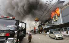 This photo taken on 23 December 2017 shows a firefighter standing in front of a burning shopping mall in Davao City on the southern Philippine island of Mindanao. Picture: AFP.