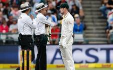 Australian fielder Cameron Bancroft is questioned by Umpires Richard Illingworth and Nigel Llong during the third day of the third Test cricket match between South Africa and Australia at Newlands cricket ground on 24 March 2018 in Cape Town. Picture: AFP