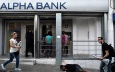People withdraw cash from ATMs in central Athens on 19 June, 2015, as a beggar lays on the pavement. Picture: AFP.