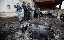 Israeli men inspect the damage caused to a house by a rocket launched by Palestinian militants from the Gaza Strip. Picture: AFP.