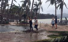 Residents clear the area of fallen trees and branches on the Hamilton Island after strong Cyclone Debbie hit the Whitsundays Islands in Queensland on 29 March, 2017. Picture: AFP.