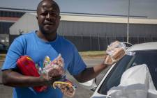 A man drops meat hampers - packets containing multiple products that cost roughly R200 - to security officials outside the Enterprise factory in Germiston. Picture: Thomas Holder/EWN