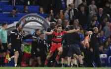 Huddersfield Town defender Tommy Smith (C) runs onto the pitch to celebrate Premier League survival after their match against Chelsea at Stamford Bridge in London on 9 May, 2018. Picture: AFP