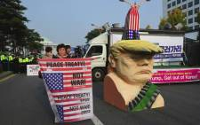 An anti-Trump protestors hold signs next to an effigy of US President Donald Trump during a rally near the National Assembly in Seoul on 8 November, 2017 as Trump is due to address the South Korea's national assembly. Picture: AFP.