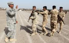 FILE. American military trainers show Iraqi soldiers how to work in a formation during a training session at the Taji base complex, which hosts Iraqi and US troops, located 30 kilometres north of the capital Baghdad. Picture: AFP.