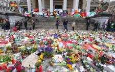 Floral tributes and candles are displayed outside the Stock Exchange in Brussels on March 27, 2016 as they lie in tribute to the victims of the coordinated terror attacks in the city claimed by the Islamic state group (IS) on March 22, in which 31 people were killed and over 300 injured. Picture: AFP.