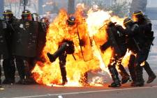 French CRS anti-riot police officers are engulfed in flames as they face protesters during a march for the annual May Day workers' rally in Paris on 1 May 2017. Picture: AFP.