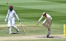 Australia's Nathan Lyon (R) sends down a delivery while West Indies batsman Marlon Samuels (L) looks on as Australia defeat the West Indies on the fourth day of the second cricket Test in Melbourne on 29 December 2015. Picture: AFP / William West.