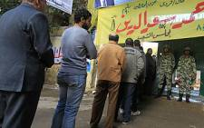Egyptian soldiers stand guard as voters queue at a polling station in the Manial neighbourhood of Cairo on 28 November 2011. Picture: AFP