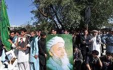Supporters of slain former President Burhanuddin Rabbani hold a poster of his image outside the compound of his home in Kabul on 21 September 2011, as they hold a peace rally. AFP
