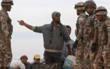 A Syrian refugee man speaks with a member of the Jordanian army as he waits to cross to the Jordanian side of the Hadalat border crossing, a military zone east of the capital Amman, after arriving from Syria. Picture: AFP.