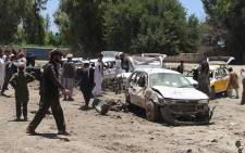 Afghan residents gather at the scene of a suicide car bomb that targeted a CIA-funded pro-government militia force at a public bus station in Khost province on 27 May  2017. A Taliban car bomber killed 14 people in Afghanistan's Khost city on May 27, in the first major attack at the start of the holy month of Ramadan that targeted a CIA-funded militia group. Picture: AFP.