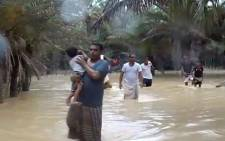 An image grab taken from an AFPTV video shows people walking through flood water as they evacuate a flooded area during a cyclone in the Yemeni island of Socotra. Picture: AFP.