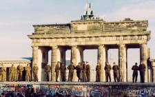 A file photo dated 11 November 1989 shows East German border guards standing on the Berlin Wall at the Brandenburg Gate in West Berlin, Germany. Picture: EPA.