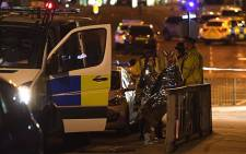 Concert goers wait to be picked up at the scene of a suspected terrorist attack during a pop concert by US star Ariana Grande in Manchester, northwest England on 23 May 2017.  Picture: AFP