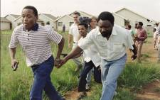 ANC Secretary General Cyril Ramaphosa (right) and a bodyguard run for cover under fire as shooting broke out during a peace tour of Katlehong with South African Communist Party Leader Joe Slovo on 9 January 1994. Picture: Walter Dhladhla/AFP.