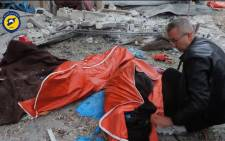 An image grab from a video released by the Syrian Civil Defence in Aleppo on 30 November 2016, reportedly shows a man covering a body lying on a street in the rebel-held district of Jubb al-Qubbeh in eastern Aleppo following government artillery fire. Picture: AFP.