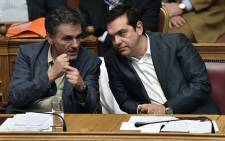 FILE: Greek Prime Minister Alexis Tsipras (R) and Finance Minister Eyclid Tsakalotos attend a parliamentary session in Athens on 15 July, 2015. Picture: AFP.