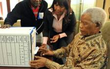 Nelson Mandela assisted by his granddaughter Ndileka Mandela and the IEC President Officer at his ward casting his special vote on 16 May 2011. Picture: GCIS