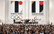 FILE: People wave Olympic flags as the logo marks of the Tokyo 2020 Olympic and Paralympic Games are unveiled at the Tokyo city hall on 24 July 2015. Picture: AFP.