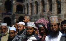 Muslim men gather to attend Friday prayers near Rome's ancient Colosseum on October 21, 2016 to protest against the closure of unofficial mosques. The Muslim community of Rome gathered by the Colosseum to pray and demonstrate against the alleged shutting down by police of unofficial mosques. Picture: AFP