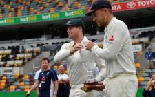 Australia's skipper Steve Smith (L) and England captain Joe Root carry the Ashes trophy at a media opportunity in Brisbane on November 22, 2017. Picture: AFP
