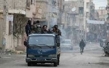 FILE:Rebels stand on the back of a pick-up truck driving through the eastern Syrian town of Deir Ezzor on 10 March, 2014. Picture: AFP.