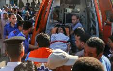 Egyptian medics unload a wounded woman from the back of an ambulance outside a hospital in Cairo's northern suburb of Shubra on 26 May 2017, following an attack in which Coptic pilgrims were gunned down following a visit to a monastery. Picture: AFP.