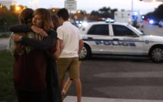 FILE: Kristi Gilroy hugs a young woman at a police checkpoint near the Marjory Stoneman Douglas High School where 17 people were killed by a gunman on 15 February 2018 in Parkland, Florida. Picture: AFP.