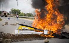 A woman and child walk past a burning barricade in Alexandra, put in place to close the road to the new clinic that was meant to be opened. Picture: Thomas Holder/EWN.