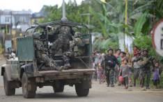 FILE: Philippine troops escort rescued civilians while a military truck covers them from sniper fire at a village on the outskirts of Marawi on the southern island of Mindanao. Picture: AFP