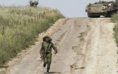 FILE: An Israeli soldier runs to direct a M113 armored personal vehicle near the Syrian border in the Israel-annexed Golan Heights on 10 May 2018. Picture: AFP.