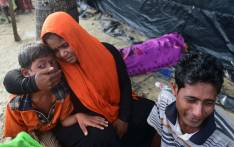 FILE: Rohingya refugees sit next to the body of their relative Anwara Begum, who died when their boat capsize during their Naf river crossing, in the Bangladeshi city of Teknaf on 14 September 2017. Picture AFP.