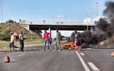 Protesters from Top Village township can be seen blocking the main road leading into Mahikeng as they continue to call for the removal of Premier Supra Mahumapelo. Police are using tear gas and rubber bullets to disperse protesters. Picture: Ihsaan Haffejee/EWN.