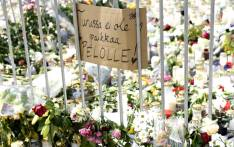 Candles, flowers and a placard reading 'There is no place for fear in Turku' have been left at the makeshift memorial for the victims of Friday's stabbings at the Turku Market Square, Finland on 20 August 2017. Picture: AFP