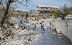 Residents bathe and clean laundry in a river 22 September 2017 in Canefield in the Caribbean island of Dominica, four days after the passage of Hurricane Maria. Picture: AFP.