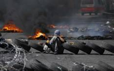 Palestinian men burn tyres during a protest in the West Bank city of Ramallah on April 6, 2018. Clashes erupted on the Gaza-Israel border Friday, AFP journalists said. Picture: AFP.