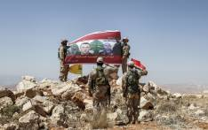 Fighters from the Lebanese Shiite Hezbollah movement raise up and salute a banner in a mountainous area around the Lebanese border town of Arsal during a tour guided by the group on 26 July, 2017, showing the photos of members of the Lebanese Army who were killed fighting militant groups along the eastern border with war-ravaged Syria. Picture: AFP.